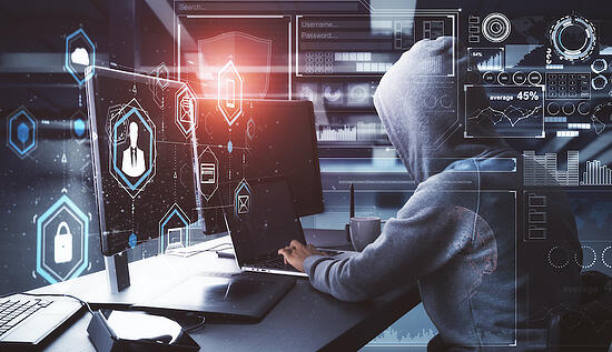 person in hoodie on computer with holograms of security around them