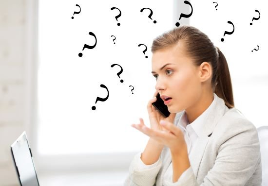 confused business woman on cellphone in front of laptop