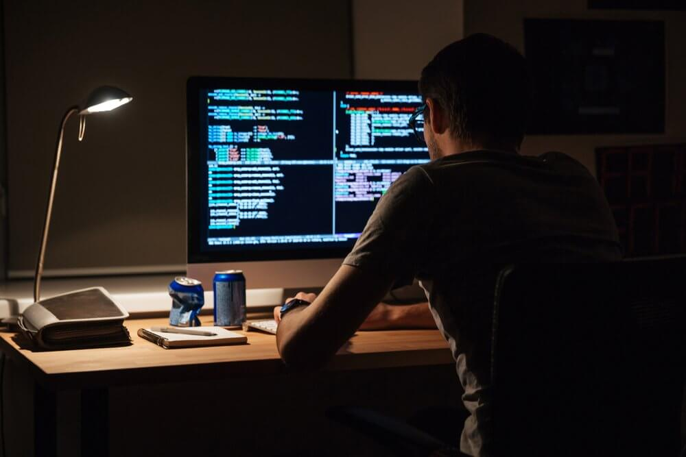 developer sitting in front of a computer with back to the camera
