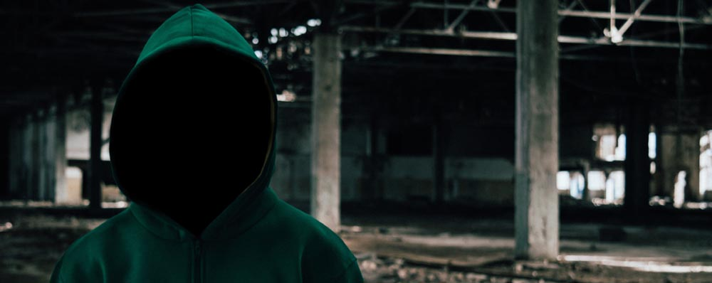 Hooded man standing in an abandoned warehouse with face hidden