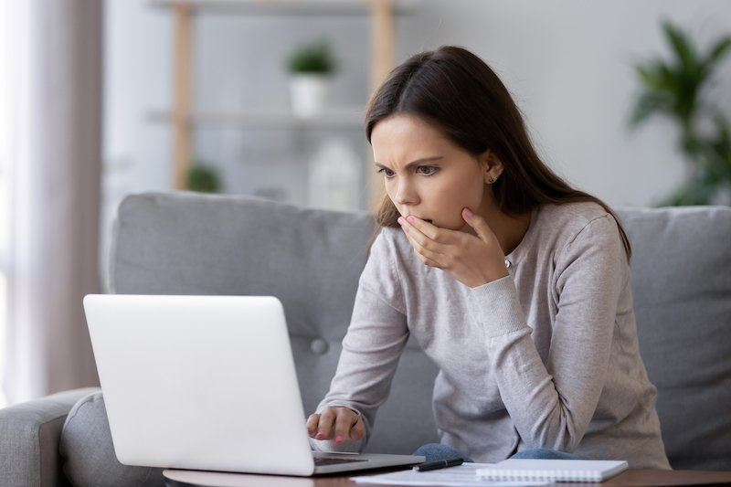 woman gasping at lead generation fraud on laptop