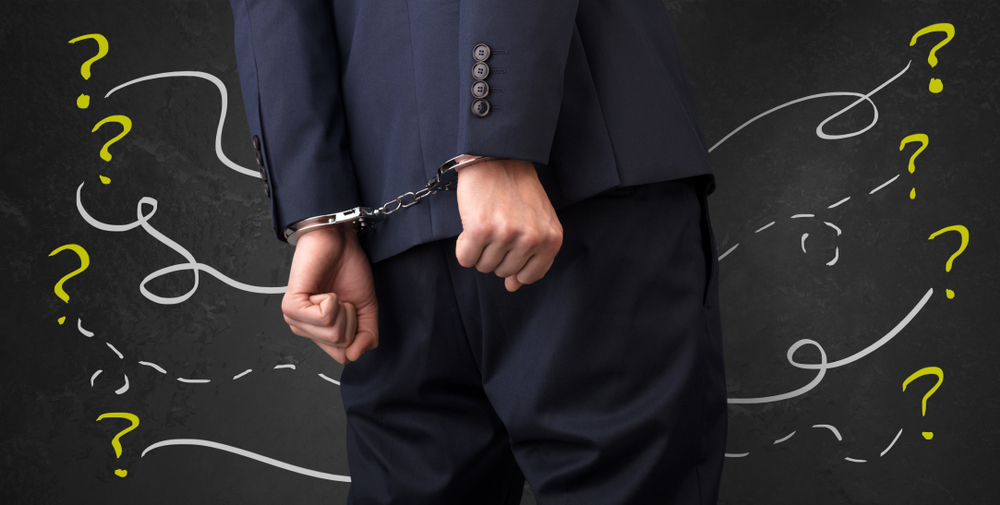 man wearing suit in handcuffs with question marks all around