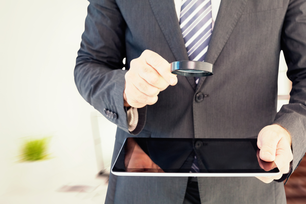 man holding magnifying glass over tablet