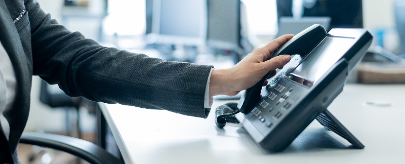 hand-picking-up-office-telephone