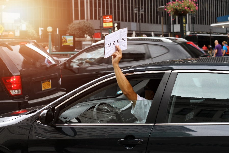 car-driver-holding-uber-sign-out-the-window-in-new-york-city